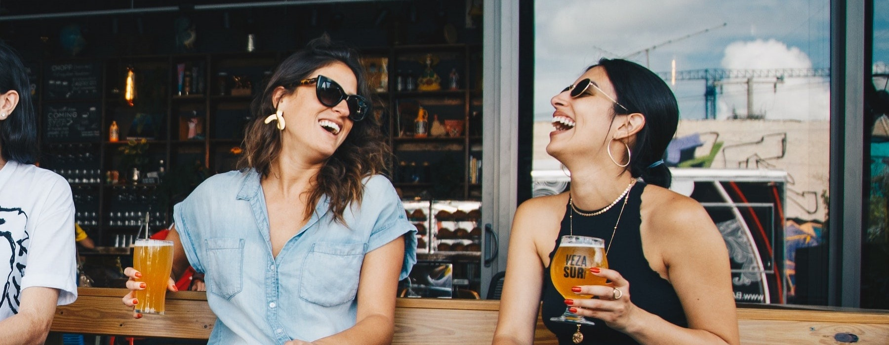 lifestyle image of two people laughing outdoors with drinks